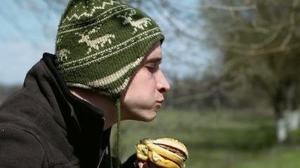 Young man eats hamburger from fast food