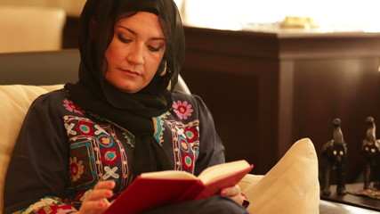 Muslim woman sitting on sofa and reading a book