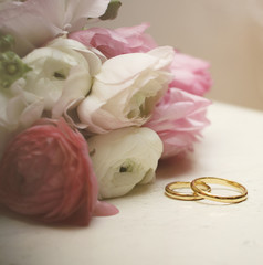 ranunculus with wedding rings on vintage table