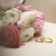 ranunculus with wedding rings on vintage table