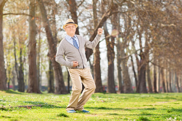 Overjoyed senior playing air guitar outdoors