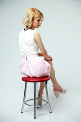 Young pensive woman sitting on the chair