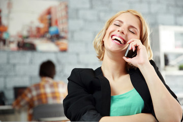 Laughing young woman talking on the office in office