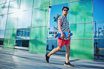 Young stylish guy in bright clothes with longboard