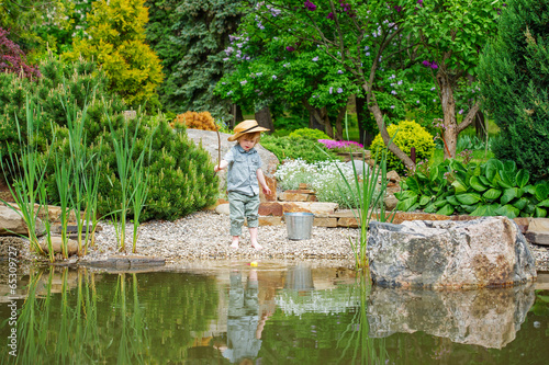 Cute little boy fishing by the pond in the beautiful garden