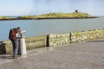 man looking to Dalkey island by binoculars