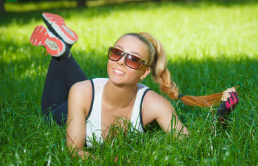 beautiful athletic girl smiling lying on the grass