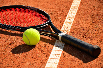 tennis ball and racket is on the carpet court