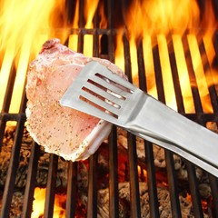Bone steak, Tongs and Hot BBQ Grate with Flames