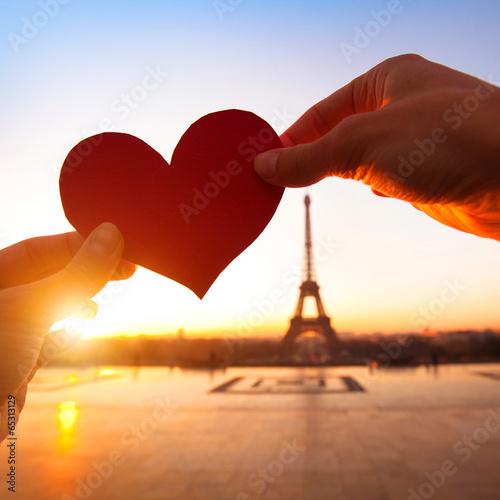 Leinwanddruck Bild heart in hands, loving couple in Paris, France