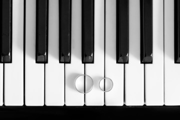 wedding rings on piano black and white closeup