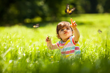 Baby girl playing with butterfly.