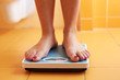 A pair of female feet on a bathroom scale - 65315304