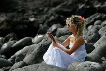 young woman using tablet on rocky beach