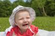Baby Girl 4 Monate mit Sonnenhut im Grünen