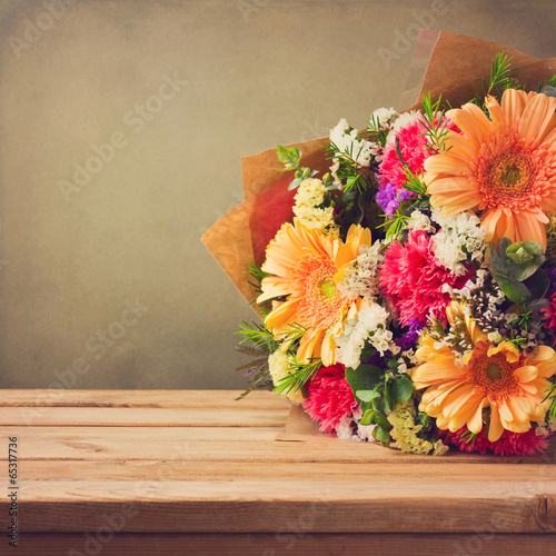 Foto op Canvas Madeliefjes Flower bouquet on wooden table over grunge background