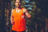 Fototapety Muscular athletic man running on the jogging track