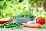Fresh organic peas in bowl on table