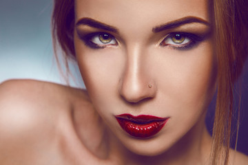 Horizontal photo of serious adult girl with nice make up in stud