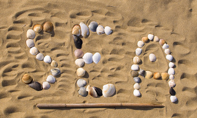 Letters written on sand with sea shells