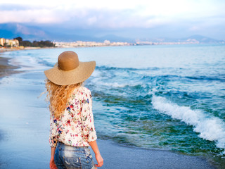 A girl in a hat at the sea coast