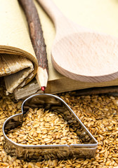 Golden flax seeds with cookbook and heart closeup