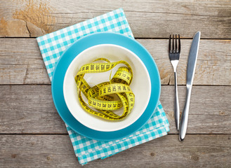 Plate with measure tape, knife and fork. Diet food