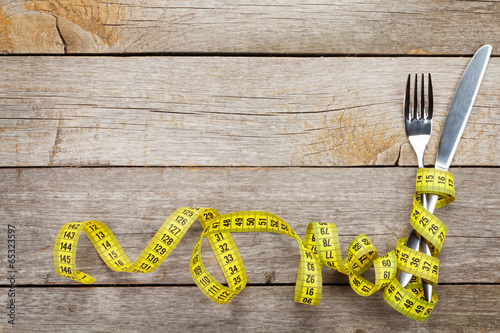 Measure tape with knife and fork. Diet food - 65323597