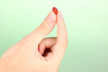 Woman's hand holding a red pill on green background close-up