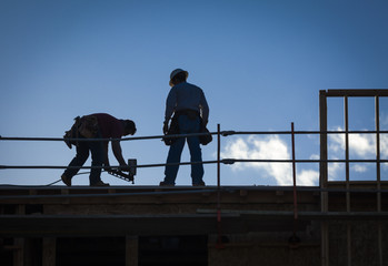 Construction Workers Silhouette on Roof
