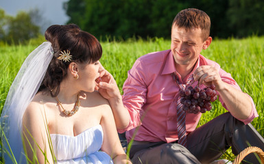 portrait of groom feeding bride with grapes at picnic