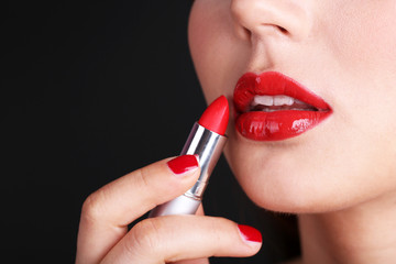 Girl with sexy red lips and pomade on dark background