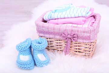 Baby clothes in basket on floor in room