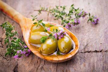 Grüne Oliven und blühender Thymian