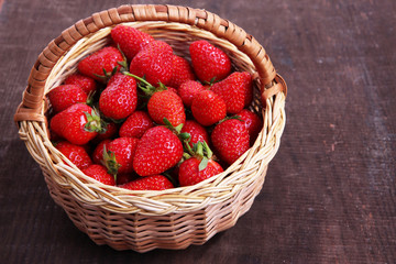 Ripe sweet strawberries in wicker basket on wooden background