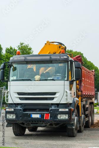 Ruspa escavatore con braccio idraulico, camion, cantiere