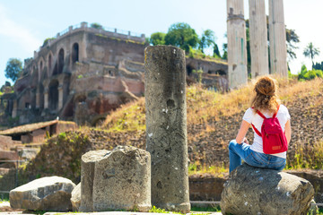 Young female tourist rests on the ruins of the Roman Forum in Ro