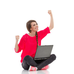 Young girl celebrates success with laptop