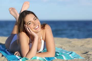 Happy woman with white perfect smile resting on the beach