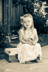 Vintage Little girl sittig on suitcase