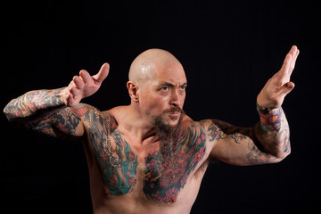 A mean-looking bodybuilder takes on a fighting stance.