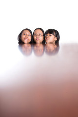 Teenage sisters with face reflection on wooden table surface