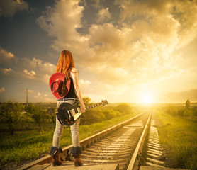 redhead woman with guitar at railway distance to sunset