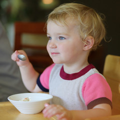 Adorable toddler girl eating ice cream in cafe
