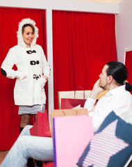 Ordinary couple trying coat in fitting-room
