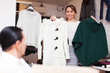 Ordinary couple choosing coat at shop