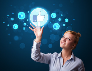 Young businesswoman pressing thumbs up button on modern social n