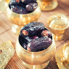 Dates fruit or kurma in metal bowl.