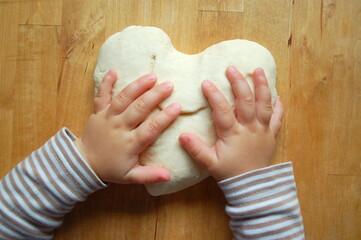 Kinderhände mit Teig in Herzform