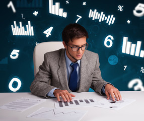 Businessman sitting at desk with diagrams and statistics
